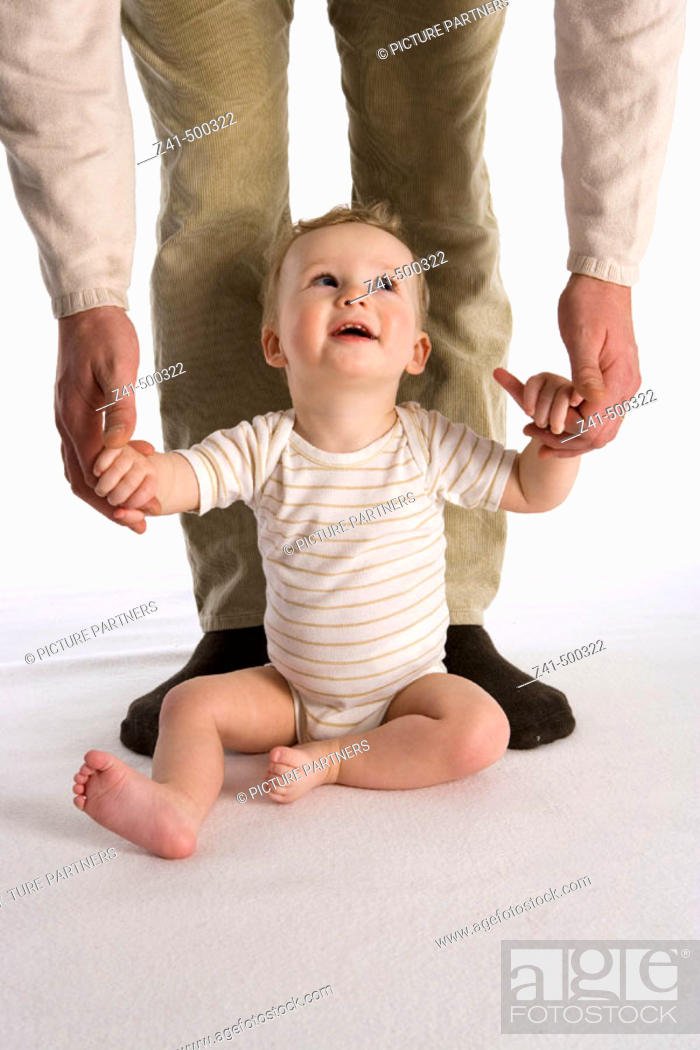 Stock Photo: Little boy sitting against his father's legs.