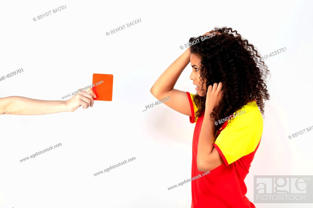Stock Photo: Portrait of a young supporter of the Spain team taking a red card.