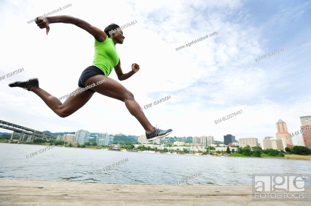 Stock Photo: African woman leaping next to river.