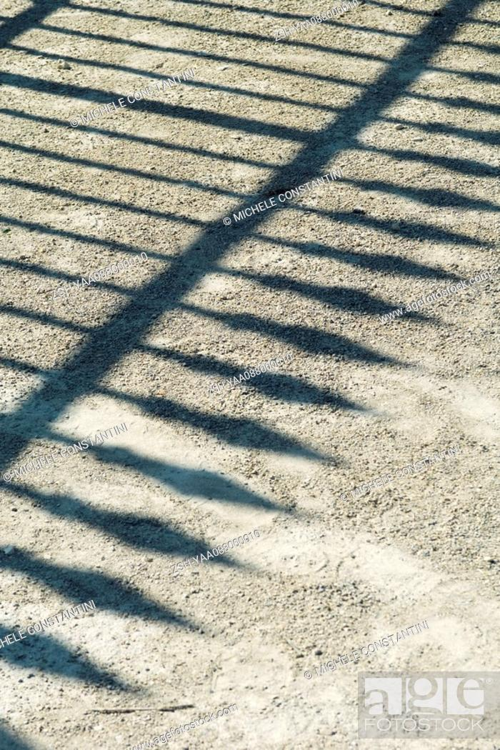 Stock Photo: Shadow of wrought iron fence on gravel.