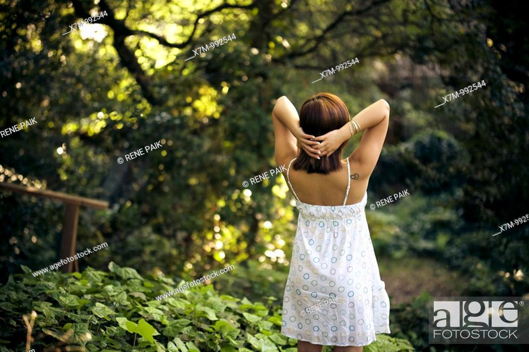Stock Photo: Beautiful young woman looking out into the forest.