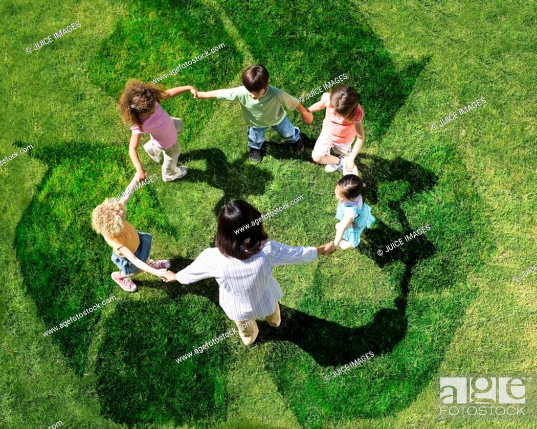 Stock Photo: Teacher and students playing on recycling symbol.