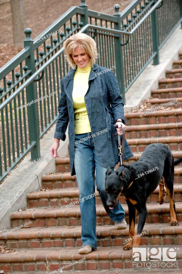 Stock Photo: Fifty year old blond woman walking a Doberman Pinscher down a stairway in a park.