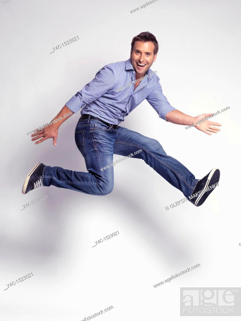 Stock Photo: Happy jumping young man wearing jeans and a shirt isolated on gray background.