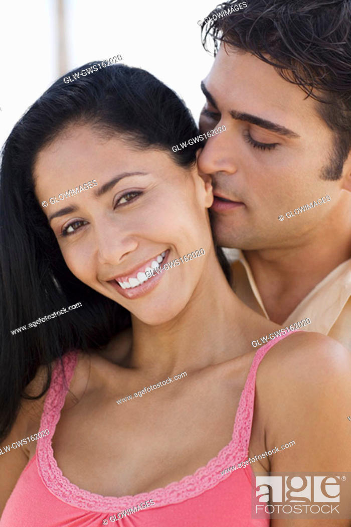 Stock Photo: Close-up of a young man embracing a young woman from behind.
