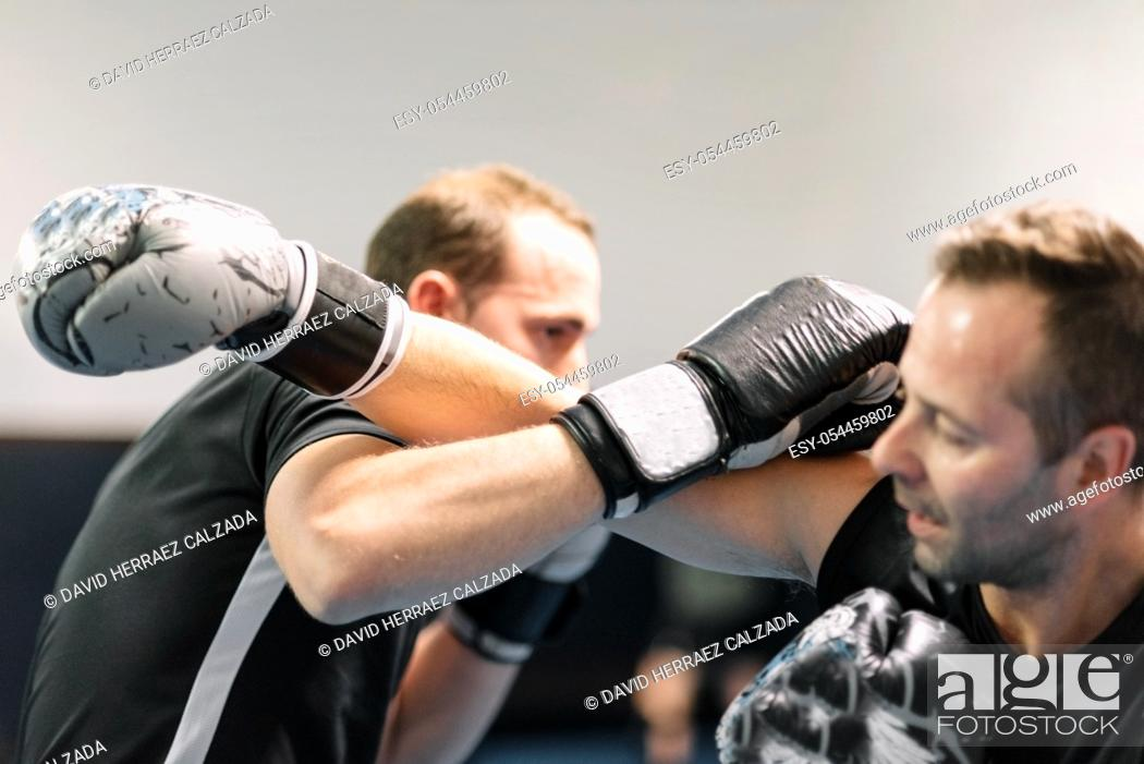 Stock Photo: young man fighter, training kick boxing with his trainer, fighting in the ring .