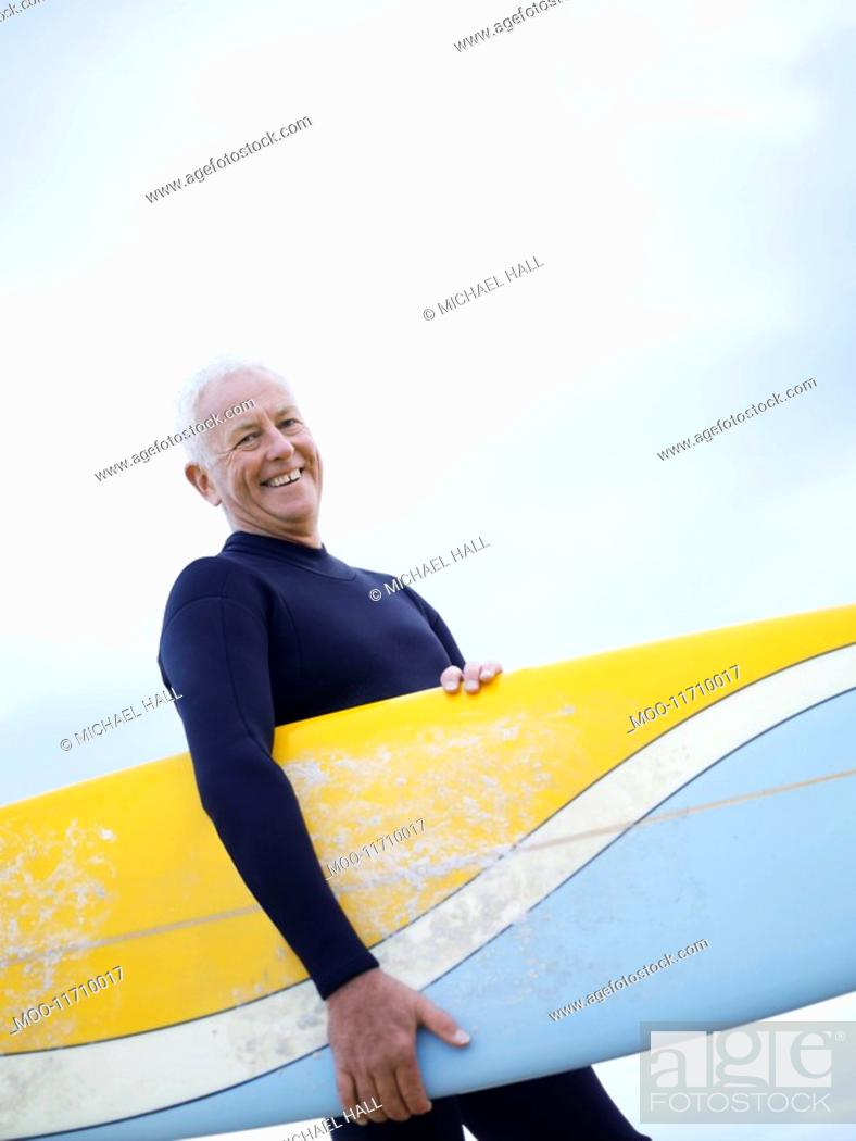 Stock Photo: Senior man carrying surfboard smiling.