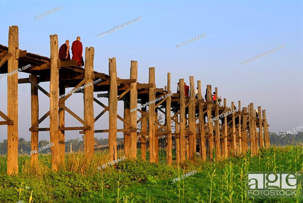 Stock Photo: Low angle view of monks on footbridge, U Bein Bridge, Amarapura, Mandalay, Myanmar.