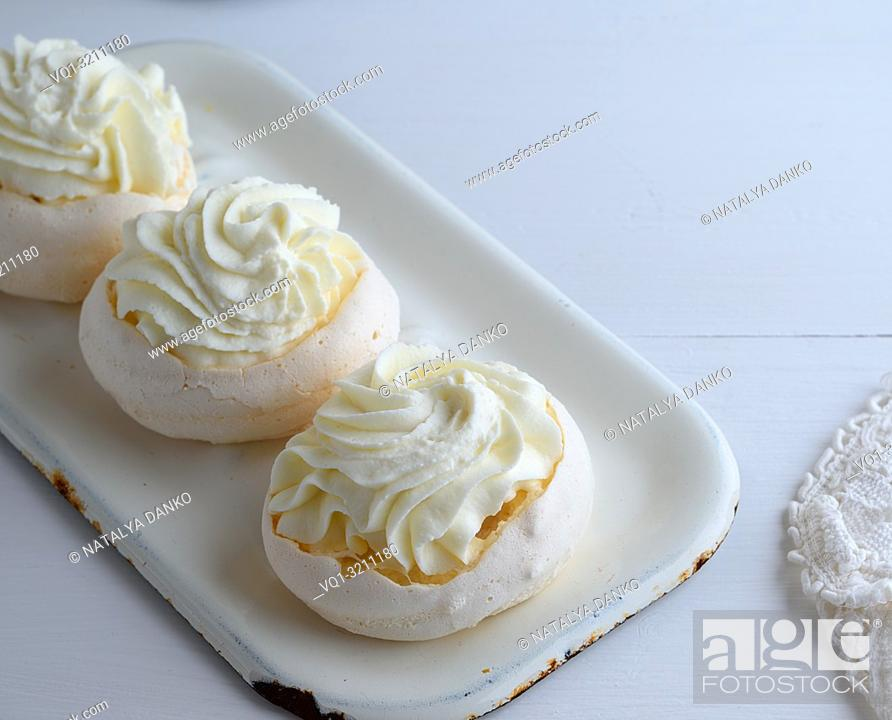 Stock Photo: baked round meringue with cream on white iron trays, top view.