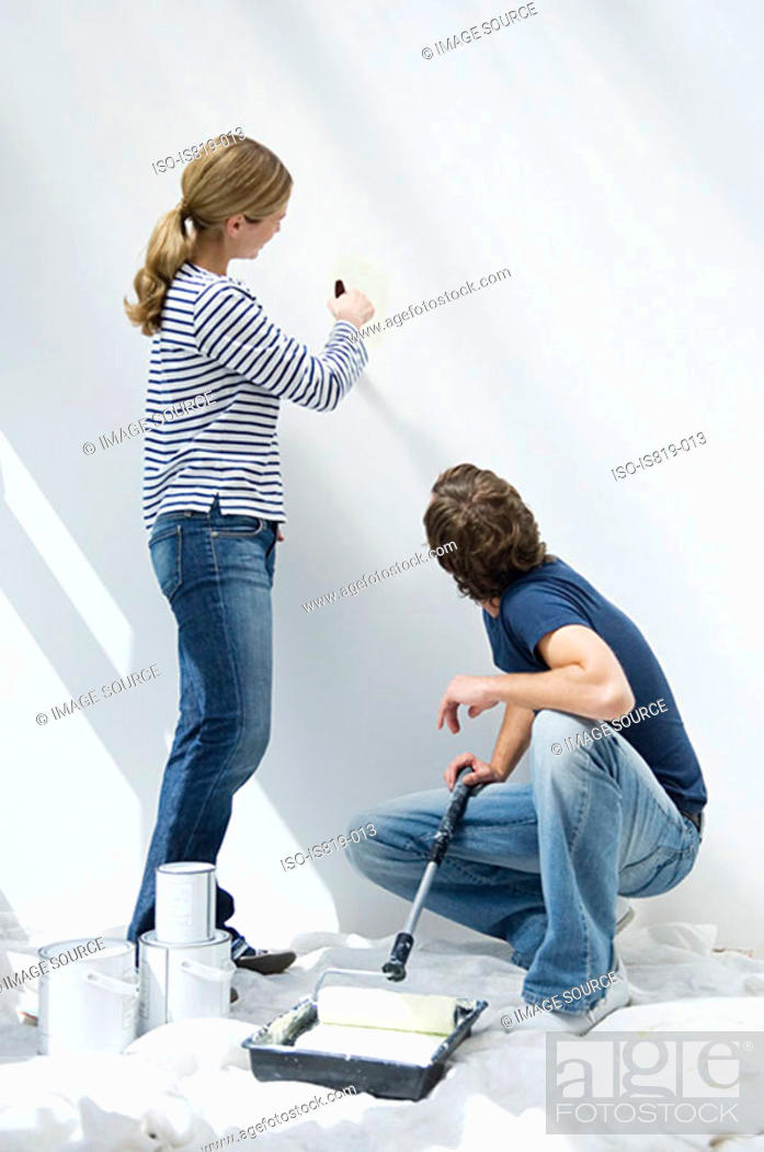 Stock Photo: Couple painting wall.