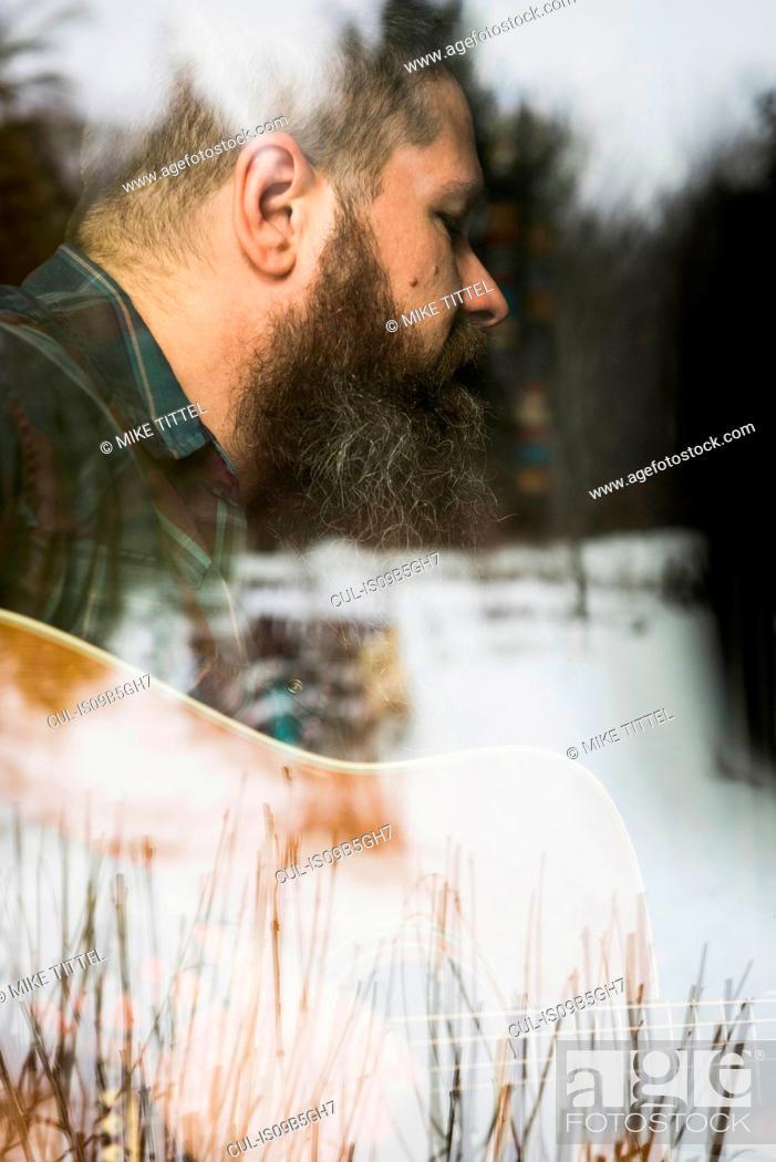 Imagen: Man with guitar beside window.