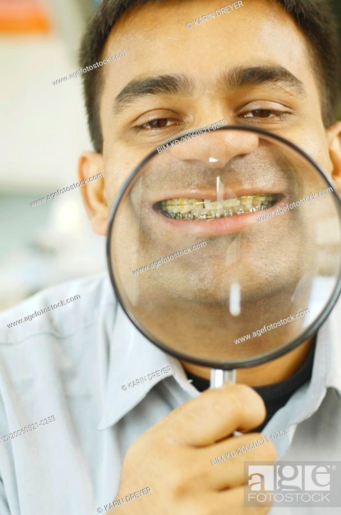 Stock Photo: Indian man holding up magnifying glass to his teeth with braces.