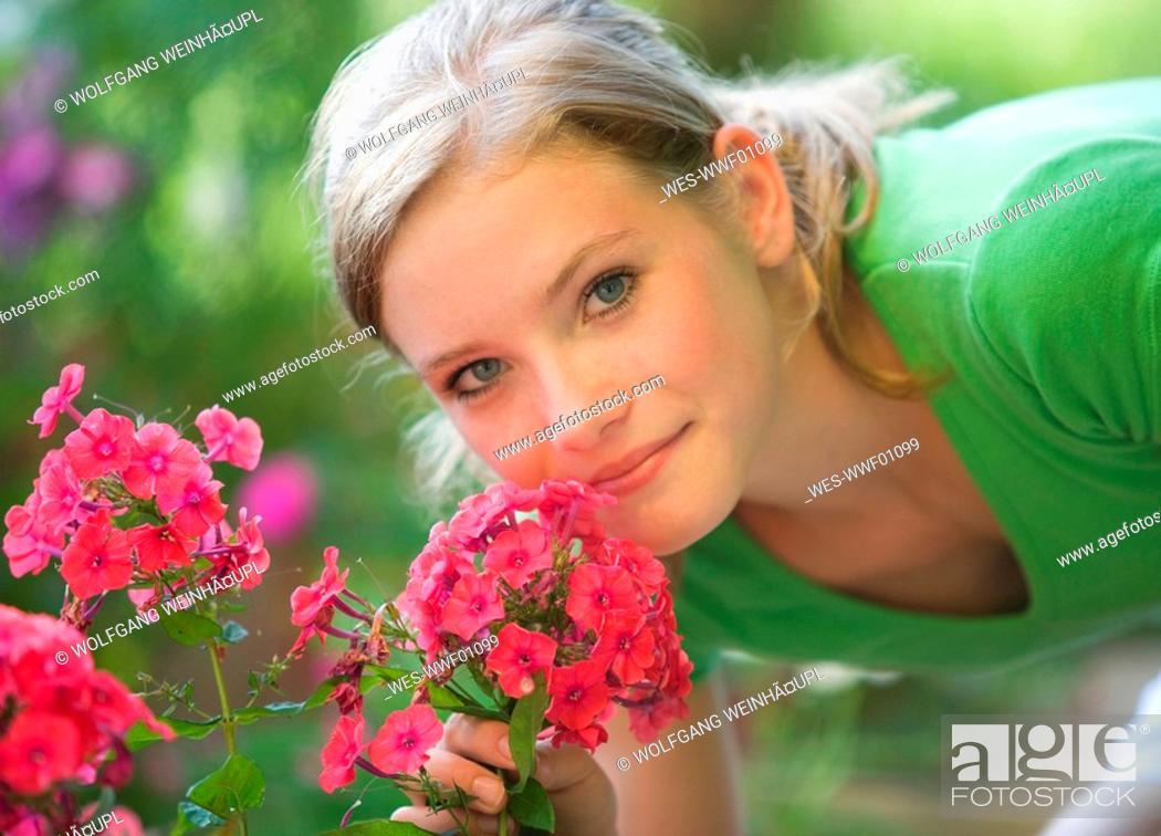 Stock Photo: Austria, Salzburger Land, Teenage girl 14-15 smelling flowers, portrait.