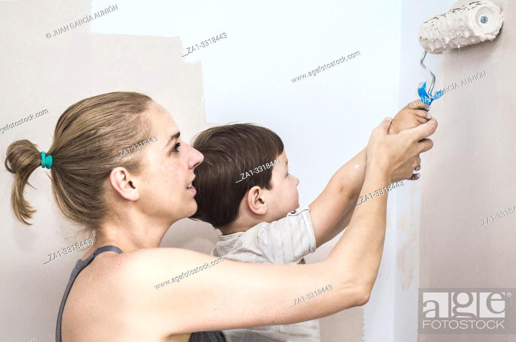 Stock Photo: Mom teachs her 3 years son painting with roller at home. Kids Helping House Chores concept.