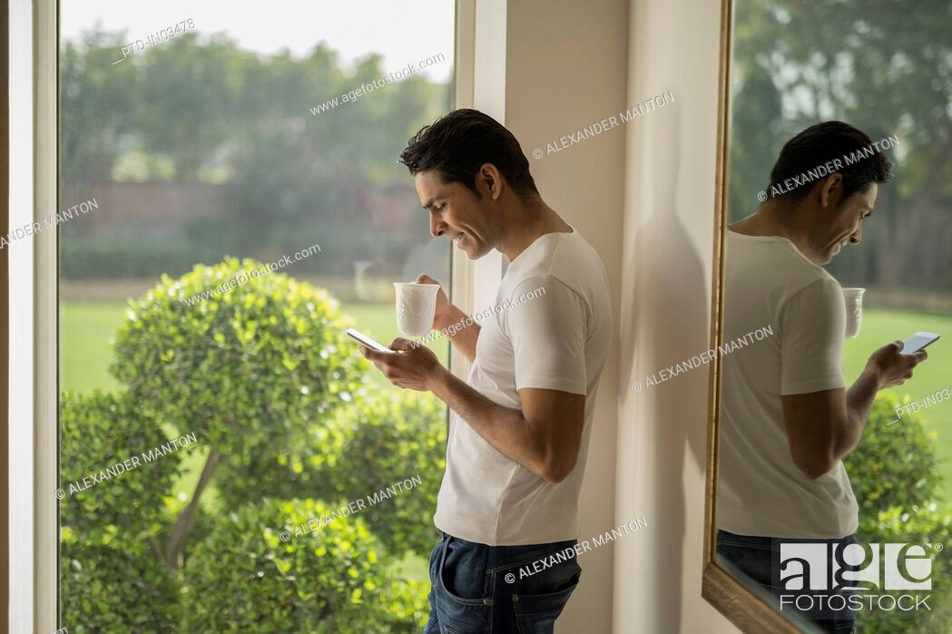 Stock Photo: India, Man at window using mobile phone and holding coffee cup.
