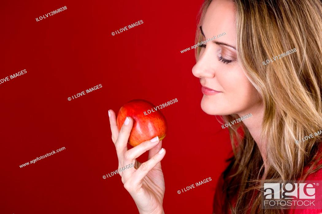 Stock Photo: A mid adult woman holding an apple.