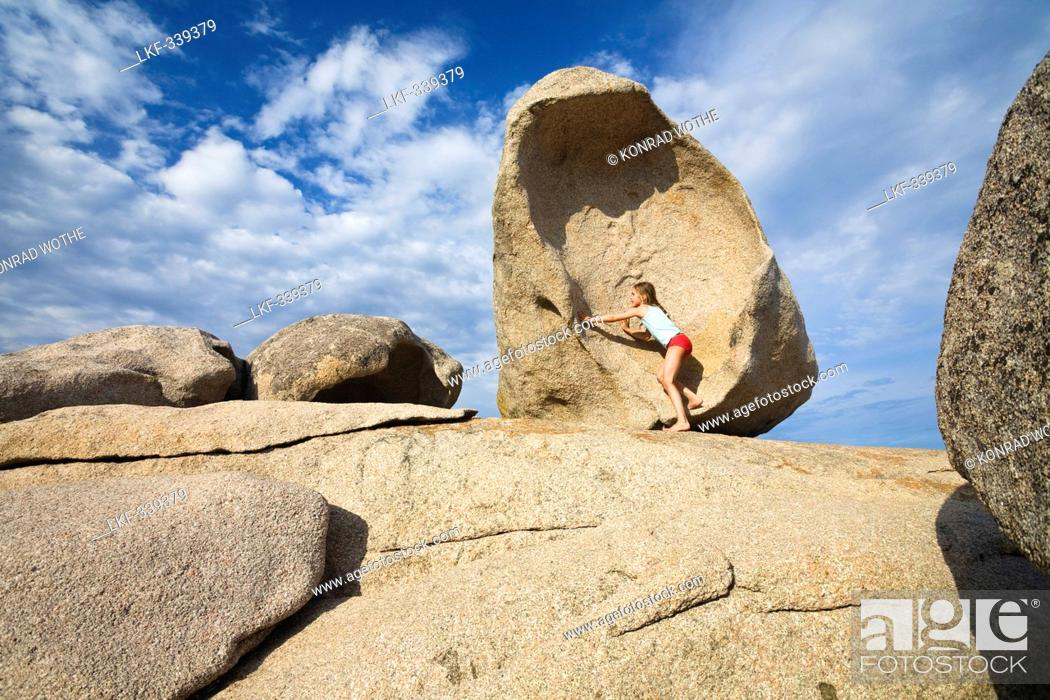 Stock Photo: Girl climbing on the rocks on the beach of Palombaggia, south-east coast, Corsica, France, Europe.