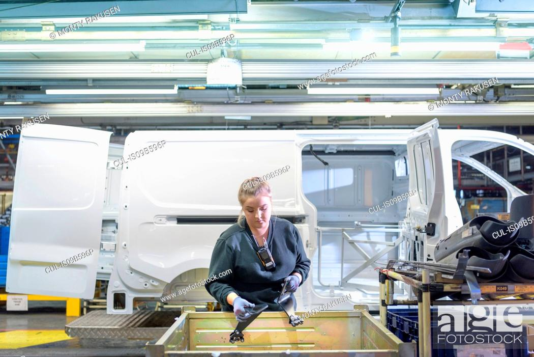Stock Photo: Female apprentice engineer on production line in car factory.