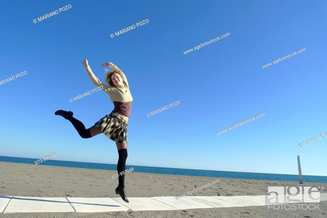 Stock Photo: Woman jumping in Torremolinos beach, Malaga province, Andalusia, Spain.