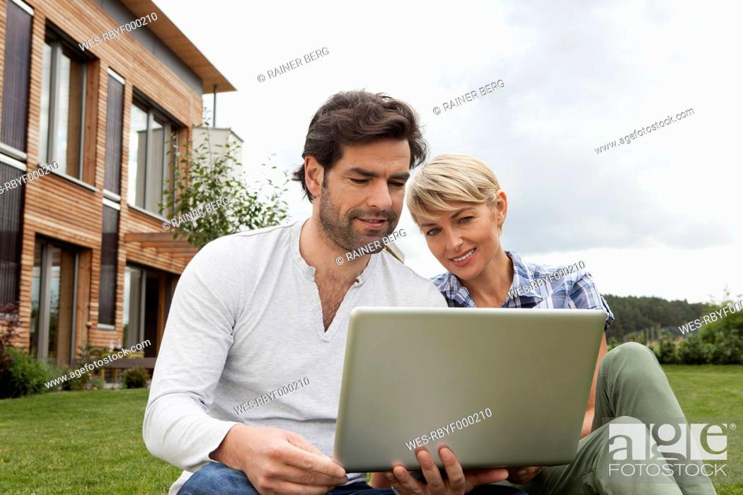 Stock Photo: Germany, Bavaria, Nuremberg, Mature couple using laptop in garden.