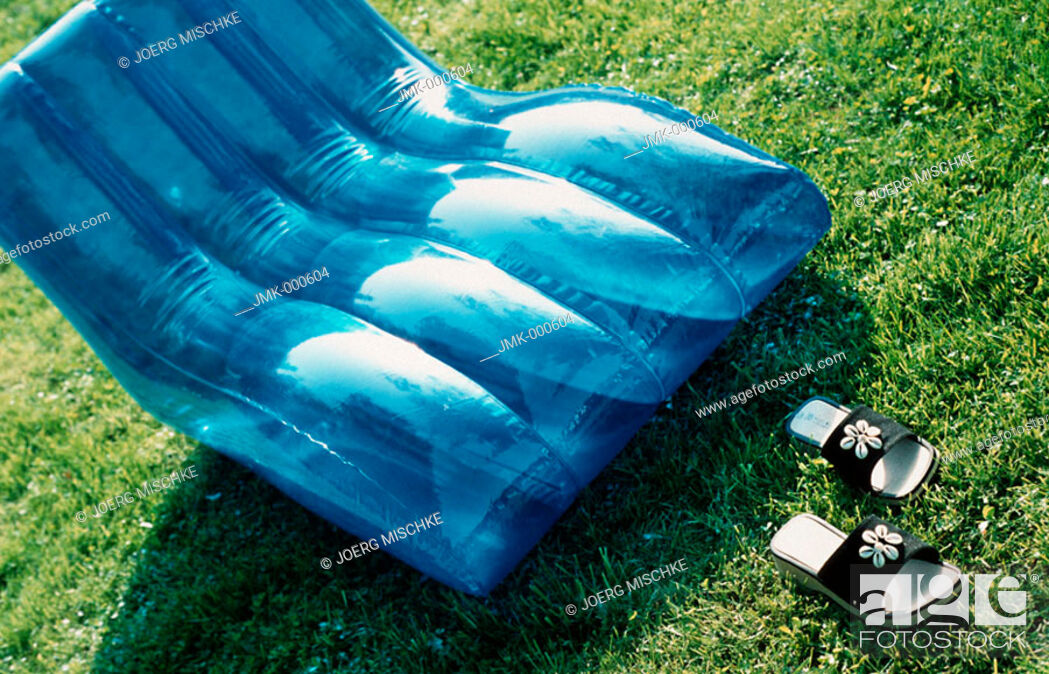 Stock Photo: A blue inflatable deckchair on the lawn in the garden.