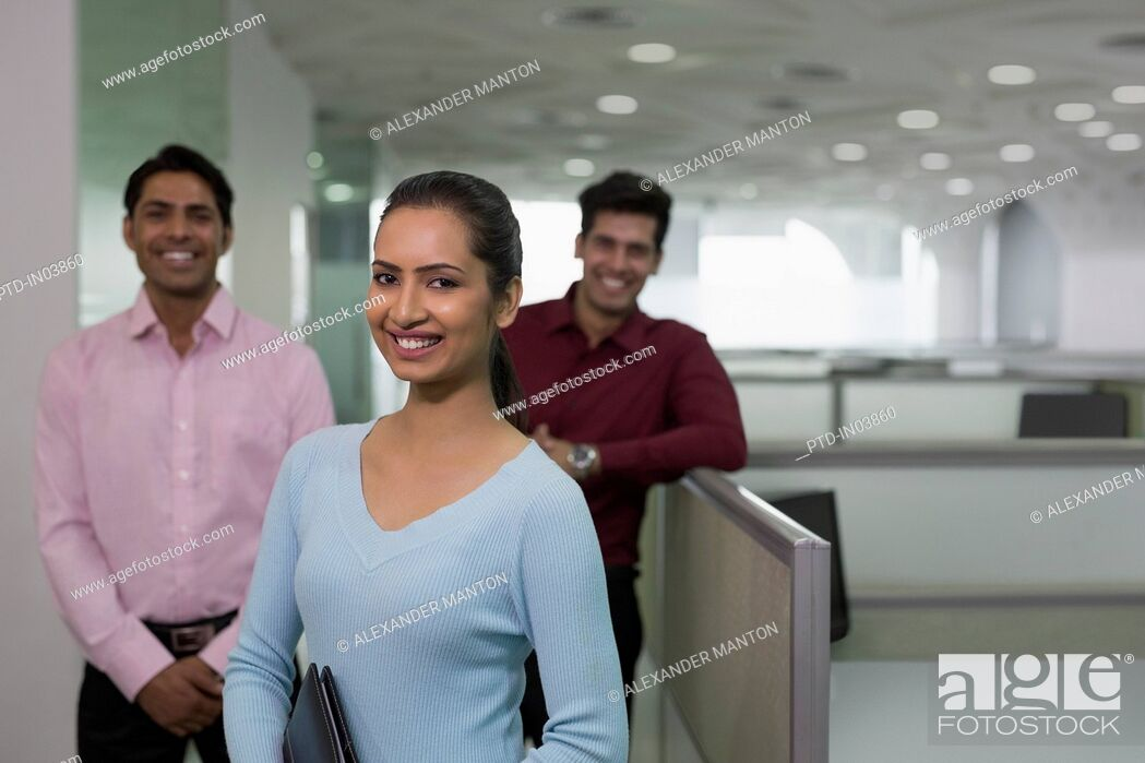 Stock Photo: India, Smiling businesswoman in front of colleagues in office.