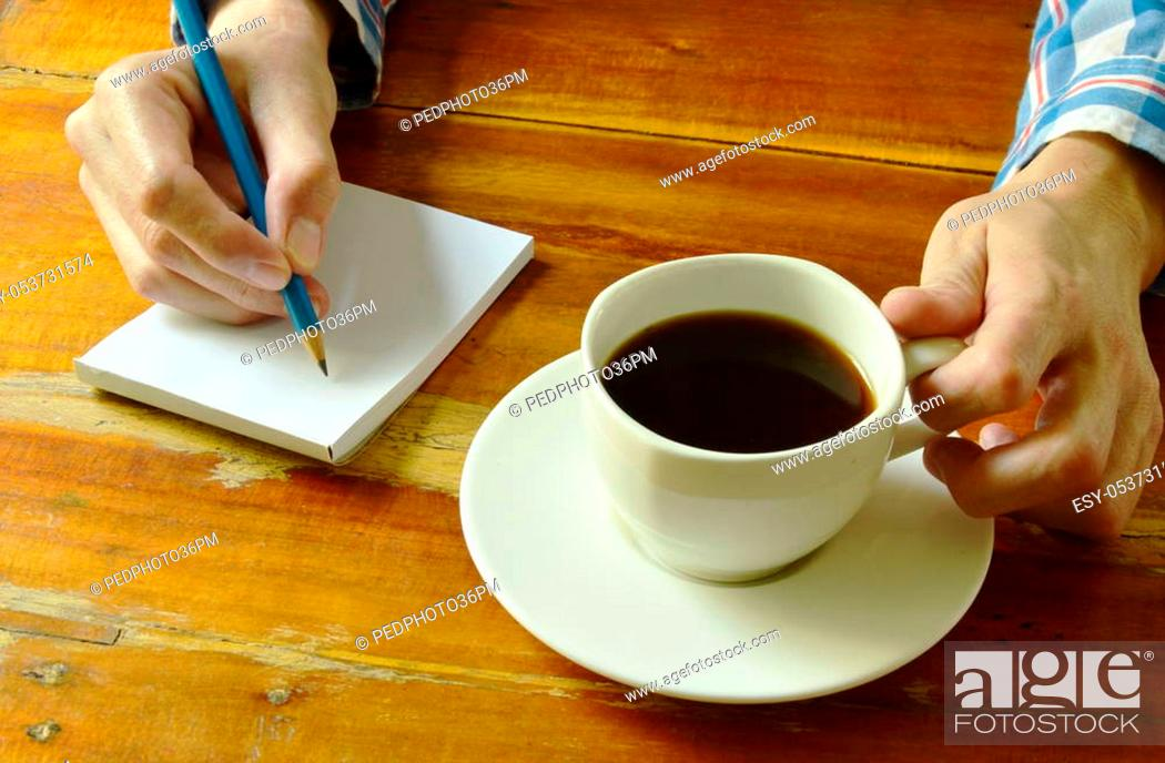 Stock Photo: hand writing on book while drinking black coffee.