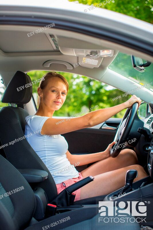 Stock Photo: Young woman driving her car, on her way home from work - doing the daily commute.