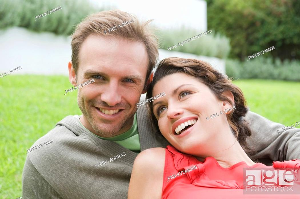 Stock Photo: Couple resting in a lawn and smiling.