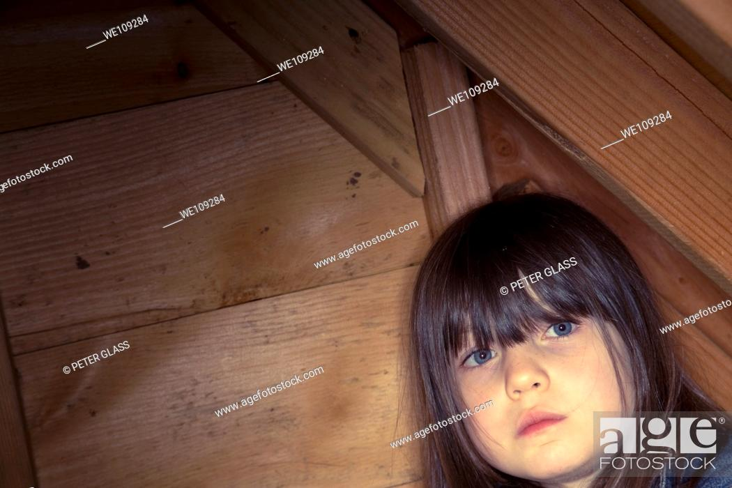 Stock Photo: Young girl in her outdoor playhouse.