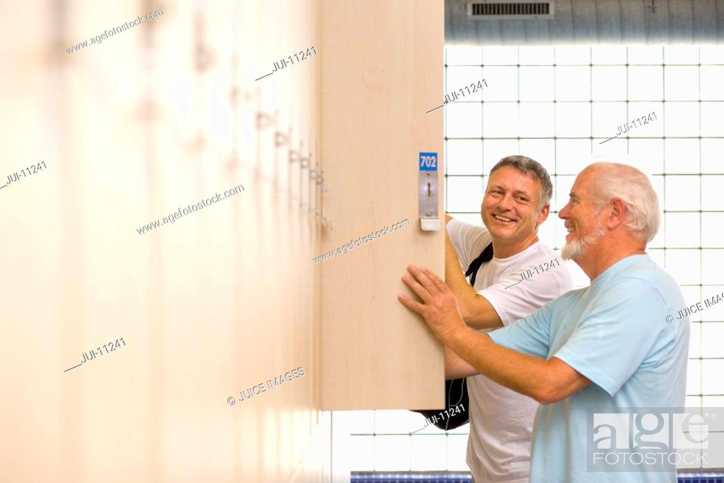 Stock Photo: Two men using lockers, smiling, side view.