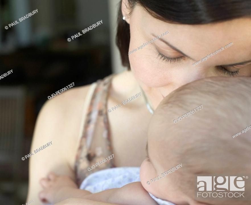 Stock Photo: Woman embracing a baby indoors.