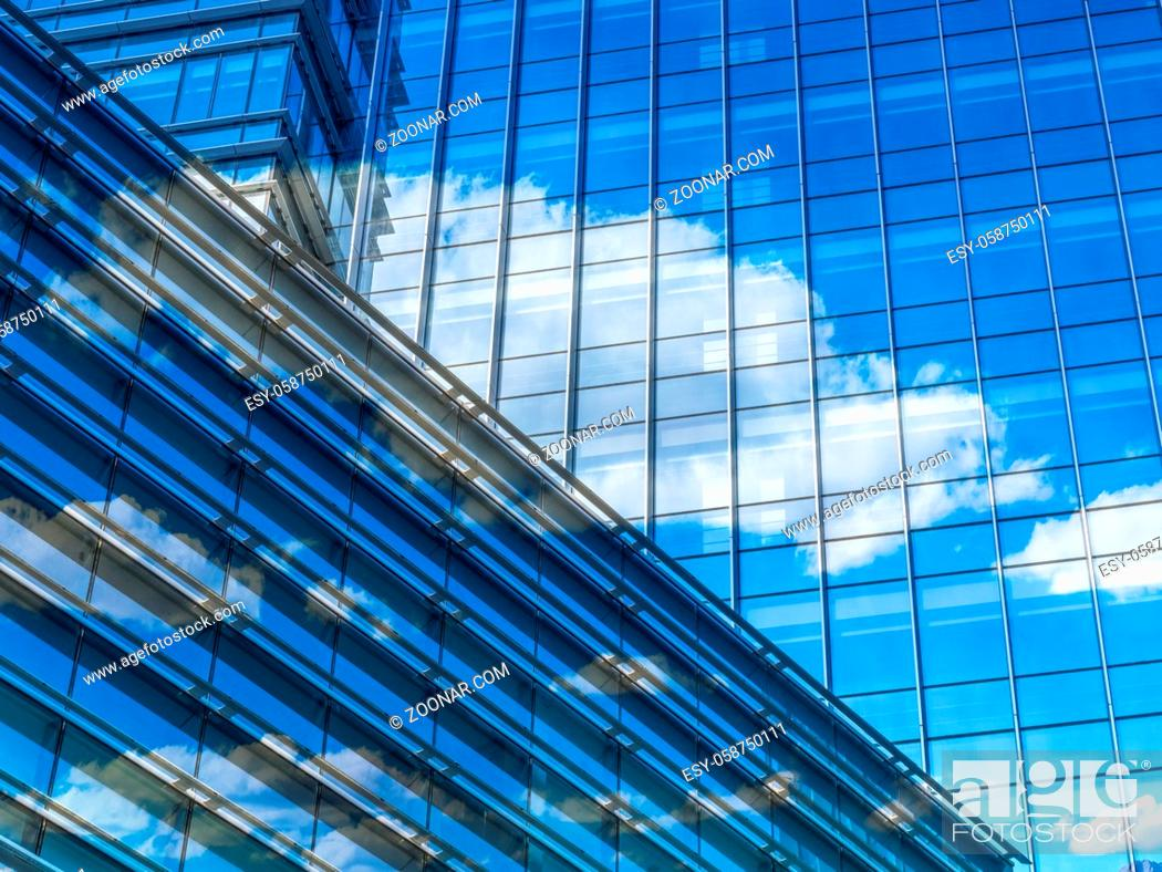 Stock Photo: modern glass building with clouds and sky reflections.