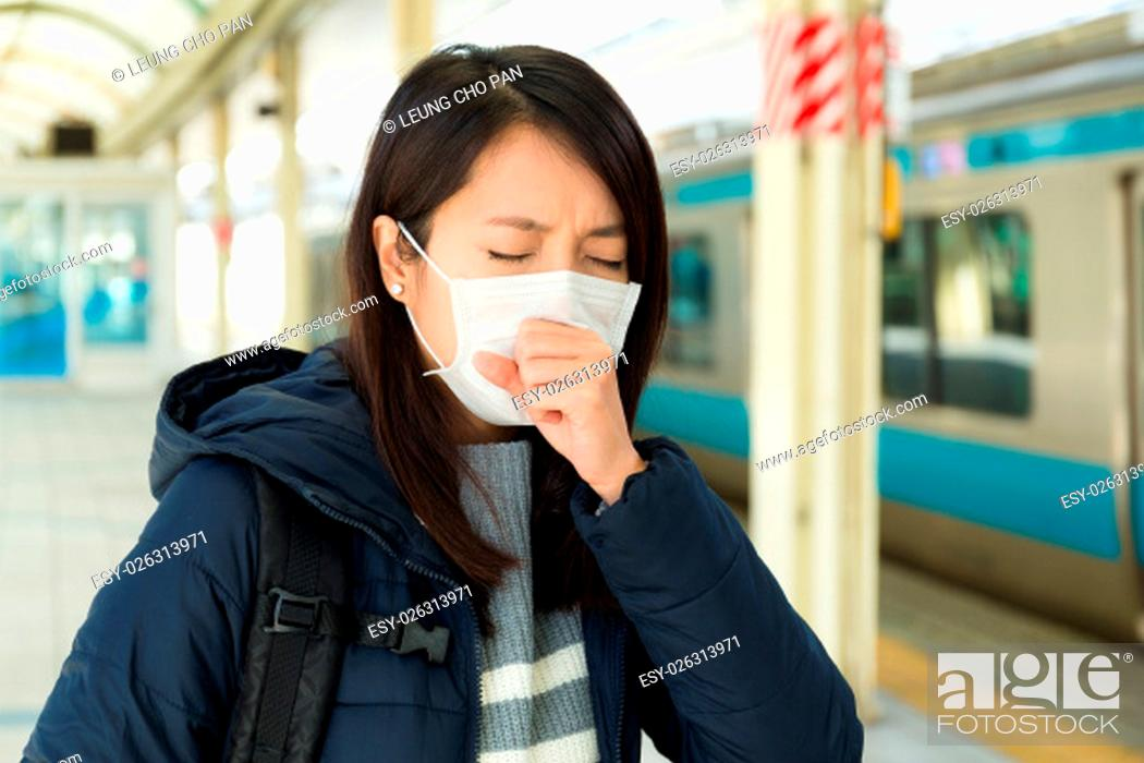 Stock Photo: Woman wearing face mask in train station.
