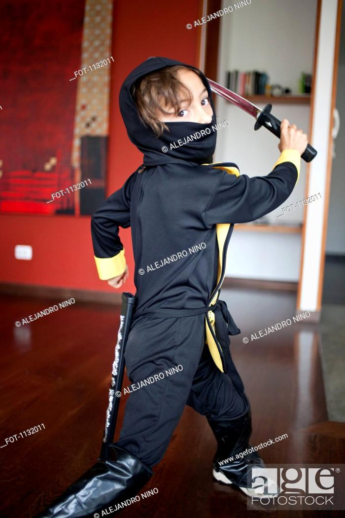 Stock Photo: A boy dressed in a ninja costume swinging a samurai sword.
