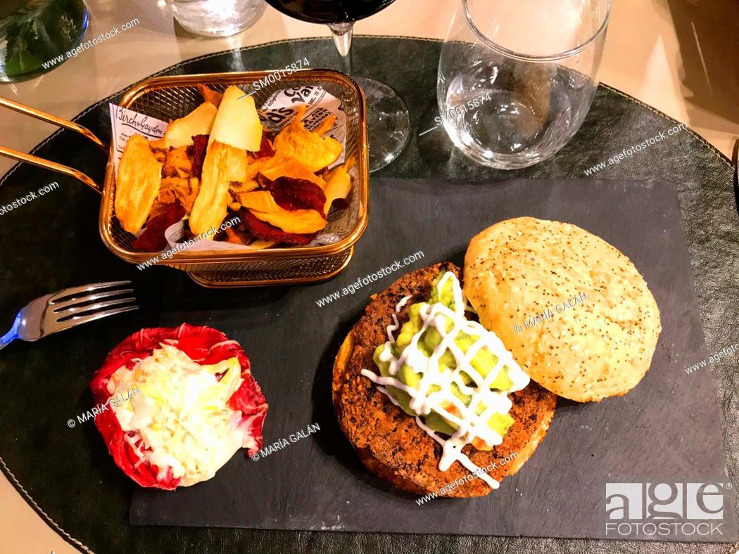 Stock Photo: Vegetarian hamburger with salad, guacamole and vegetarian chips.