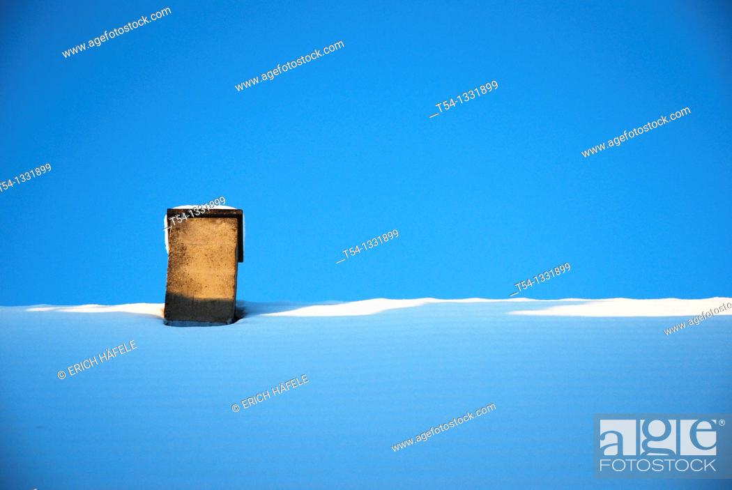 Stock Photo: Chimney on a snow-covered roof.