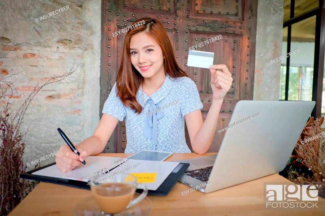 Stock Photo: Photo of a beautiful young female shopping online and paying with a credit card. Credit card information is fictitious.
