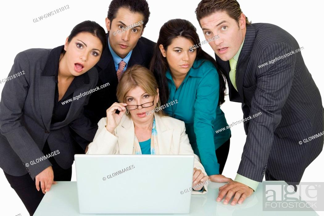 Stock Photo: Portrait of a businesswoman adjusting her eyeglasses and two businesswomen with two businessmen standing beside her.