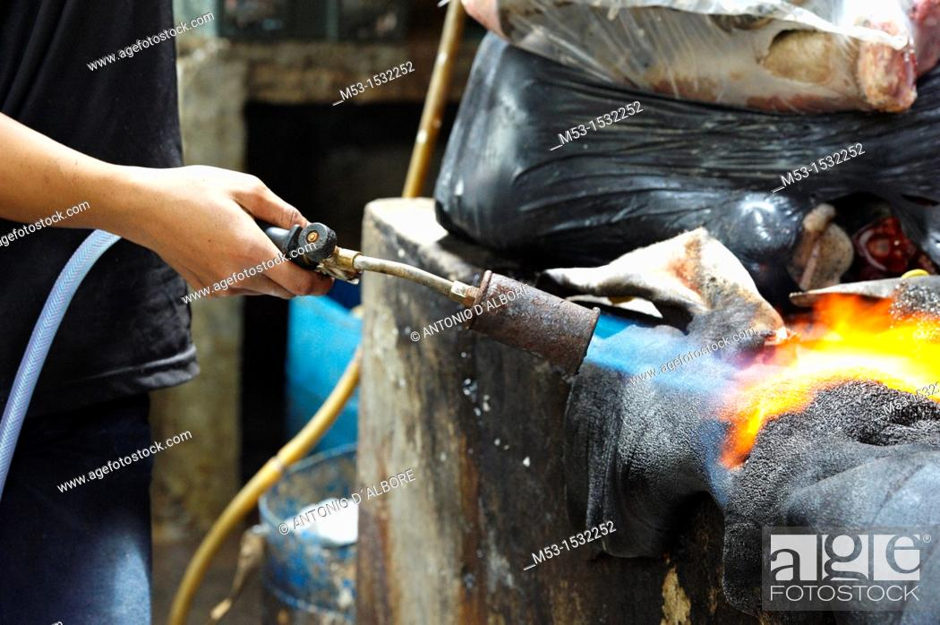Stock Photo: Burning cow skin with a gas burner  The skin is later cleaned from burned pieces and sold as ingredient for soup and other Malay recipes  Kuala Lumpur  Malaysia.
