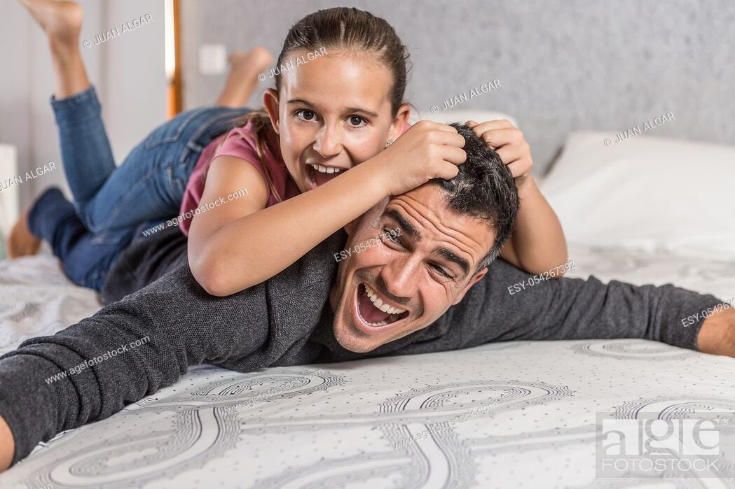 Stock Photo: father playing with his daughter and she pulls his hair.