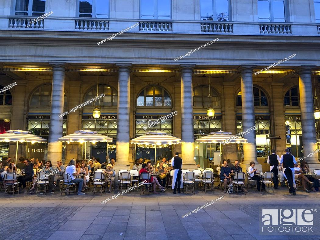 Imagen: Paris, France, Crowd of People Sharing Drinks, Outside, in French Cafe terrace, Palais Royale Neighborhood 'Le Nemours', Evening.