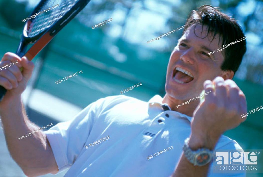 Stock Photo: Mid adult man holding a tennis racket raising his hands in excitement.