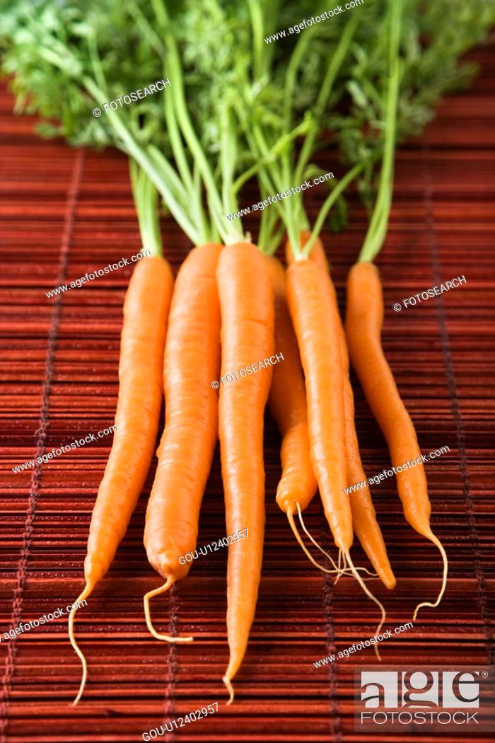 Stock Photo: Close up of orange carrots with green tops against bamboo mat.