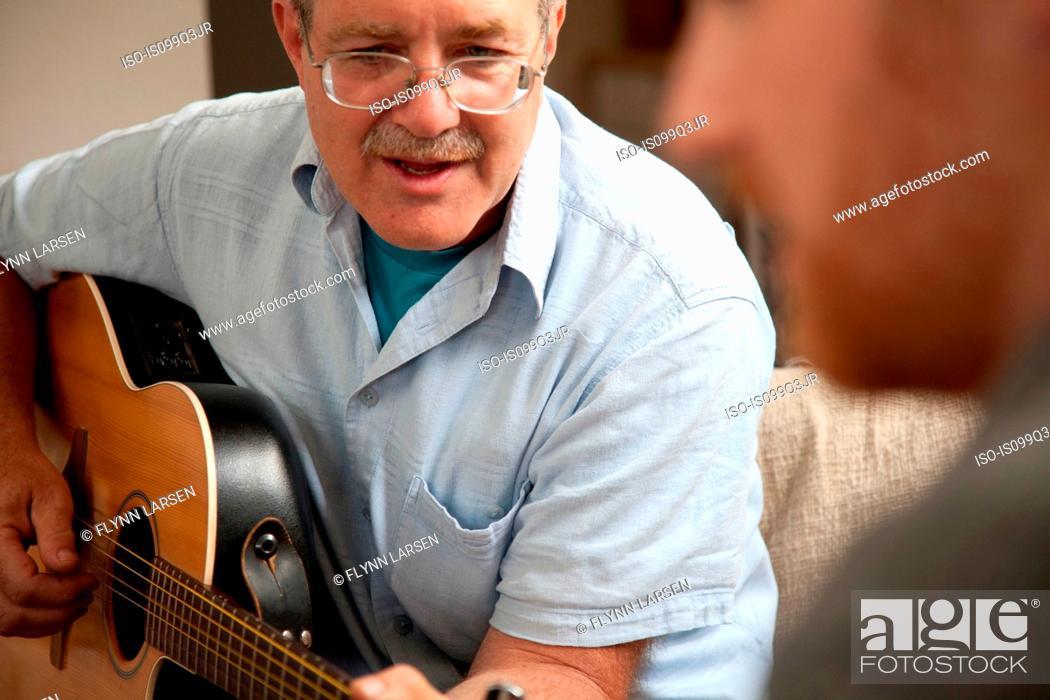 Imagen: Mature man playing guitar.