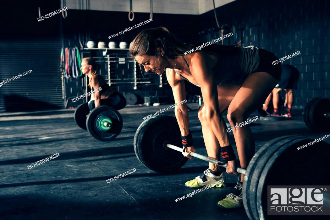 Stock Photo: Women training with barbells in gym.