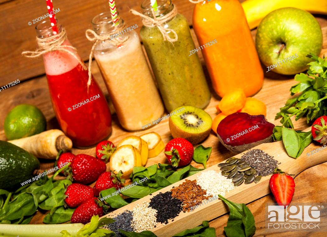Imagen: Assortment of fruit and vegetable smoothies in glass bottles with straws on wooden background.