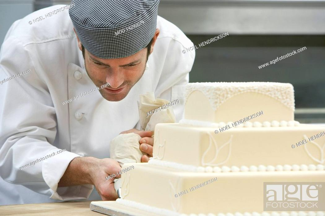 Stock Photo: Male chef icing wedding cake in kitchen.