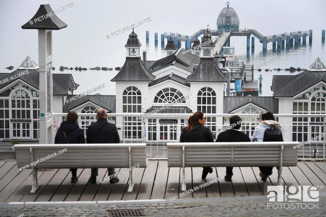 Imagen: 09 May 2020, Mecklenburg-Western Pomerania, Sellin: Tourists sit on a bench on the beach promenade in front of the pier in the Baltic resort Sellin.