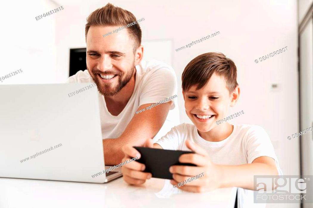 Stock Photo: Portrait of a cheerful young father and his son having fun time together at home while using laptop and playing games on mobile phone.
